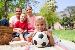 Kleines blondes Mädchen, das eine Fußballkugel anhält Stockfoto