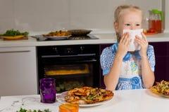 Kleines blondes Mädchen, das eine große Platte der Pizza isst Stockfotos