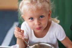 Kleines blondes Mädchen, das an einem Picknick zu Mittag isst Lizenzfreie Stockfotos