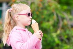 Kleines blondes Mädchen, das Eiscreme isst Lizenzfreie Stockfotografie