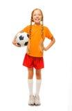 Kleines blondes Mädchen, das Fußball lokalisiert hält Lizenzfreies Stockfoto