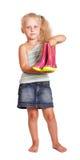 Kleines blondes Mädchen, das Gummistiefel lokalisiert steht und hält Lizenzfreie Stockfotos
