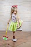 Kleines blondes Mädchen, das Hausarbeiten allein tut Stockfoto