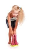 Kleines blondes Mädchen, das hinunter das Halten von Gummistiefeln lokalisiert verbiegt Stockfotos