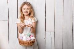 Kleines blondes Mädchen, das Korb mit gemalten Eiern hält Ostern-Tag Stockfoto