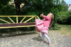 Kleines blondes Mädchen, das mit den angehobenen Händen unter Baumblumenblumenblättern auf dem Boden steht stockfotografie