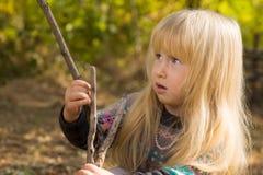 Kleines blondes Mädchen, das mit einer hölzernen Niederlassung spielt Stockfotografie