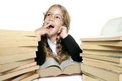 Kleines blondes Mädchen, das mit Lots Büchern lächelt Lizenzfreie Stockfotografie