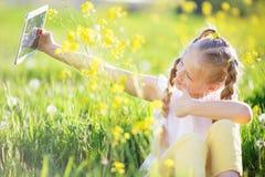 Kleines blondes Mädchen, das selfie auf dem gelben Gebiet nimmt Stockbilder