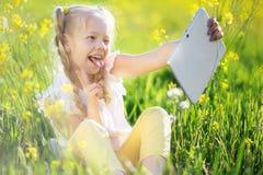Kleines blondes Mädchen, das selfie auf dem gelben Gebiet nimmt Stockbild