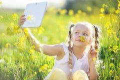 Kleines blondes Mädchen, das selfie auf dem gelben Gebiet nimmt Lizenzfreie Stockbilder