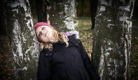 Kleines blondes Mädchen, das sich träumerisch auf der Birke lehnt Stockfotografie