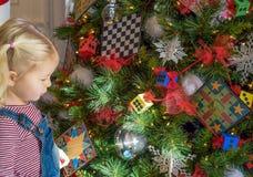 Kleines blondes Mädchen, das verzierten Weihnachtsbaum betrachtet Lizenzfreies Stockfoto