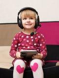 Kleines blondes Mädchen in den Kopfhörern mit der Tablette Lizenzfreie Stockbilder