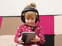 Kleines blondes Mädchen in den Kopfhörern mit der Tablette Lizenzfreie Stockfotografie