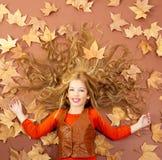 Kleines blondes Mädchen des Herbstfalles auf getrocknetem Baum verlässt Lizenzfreies Stockfoto