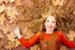Kleines blondes Mädchen des Herbstfalles auf getrocknetem Baum verlässt Lizenzfreie Stockbilder