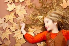 Kleines blondes Mädchen des Herbstfalles auf getrocknetem Baum verlässt Stockbild