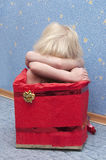 Kleines blondes Mädchen in einem Kasten Stockfoto