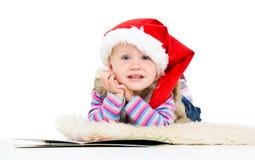 Kleines blondes Mädchen in einer Pelzjacke und einer roten Sankt in Kappe Lizenzfreie Stockfotografie