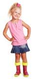 Kleines blondes Mädchen Gute in der Bluse, Rock, Gummistiefel lokalisiert Lizenzfreies Stockbild