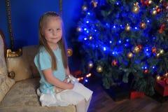 Kleines blondes Mädchen im blauen und weißen Kleid Stockfoto