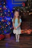 Kleines blondes Mädchen im blauen und weißen Kleid Stockbild