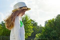 Kleines blondes Mädchen im Freien mit dem langen gelockten Haar im Strohhut, Kopienraum Stockfotografie
