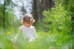 Kleines blondes Mädchen im grünen Gras Lizenzfreie Stockbilder
