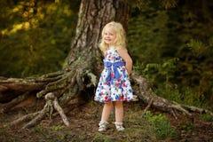 Kleines blondes Mädchen im hellen Kleid und im Hut in einem Kiefernwald-smili Lizenzfreies Stockbild