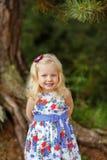 Kleines blondes Mädchen im hellen Kleid und im Hut in einem Kiefernwald-smili Lizenzfreie Stockfotografie