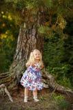 Kleines blondes Mädchen im hellen Kleid und im Hut in einem Kiefernwald-smili Stockfoto