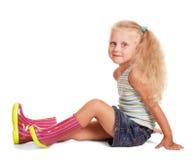 Kleines blondes Mädchen im Rock, Bluse, Gummistiefelsitzen lokalisiert Stockbild