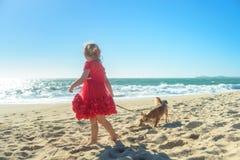 Kleines blondes Mädchen im roten Kleid mit Hund auf dem Strand Stockfoto