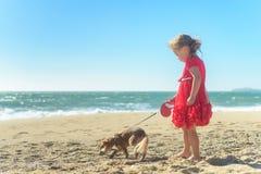 Kleines blondes Mädchen im roten Kleid mit Hund auf dem Strand Stockbilder