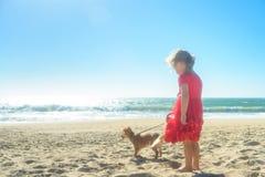 Kleines blondes Mädchen im roten Kleid mit Hund auf dem Strand Lizenzfreie Stockbilder