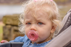 Kleines blondes Mädchen im Spaziergänger mit rosa Friedensstifter Lizenzfreie Stockfotos