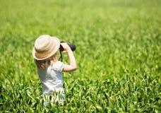 Kleines blondes Mädchen im Strohhut, der durch Ferngläser schaut Stockfoto