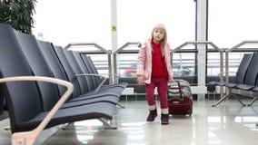 Kleines blondes Mädchen im Wintermantel mit dem Koffer, der auf einem schwarzen Stuhl in einer Wartehalle im Flughafen sitzt stock video footage
