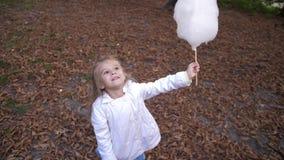 Kleines blondes Mädchen isst süße Zuckerwatte im Stadtpark Schönes kleines Mädchen, das Süßigkeitglasschlacke isst Kinderessen stock video