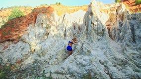 Kleines blondes Mädchen klettert auf und ab Steine durch feenhaften Strom stock footage
