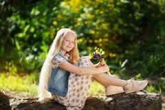 Kleines blondes Mädchen mit Blumenstrauß von Blumen Stockfotografie