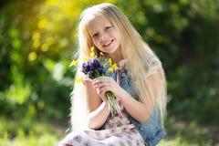 Kleines blondes Mädchen mit Blumenstrauß von Blumen Stockbilder