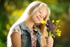 Kleines blondes Mädchen mit Blumenstrauß von Blumen Lizenzfreie Stockbilder