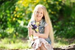 Kleines blondes Mädchen mit Blumenstrauß von Blumen Lizenzfreies Stockfoto