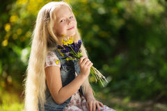 Kleines blondes Mädchen mit Blumenstrauß von Blumen Lizenzfreies Stockbild