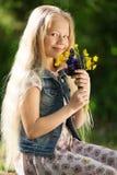 Kleines blondes Mädchen mit Blumenstrauß von Blumen Stockfoto