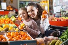 Kleines blondes Mädchen mit der Brunettemutter, die Mandarinen an betrachtet Lizenzfreies Stockbild