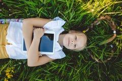 Kleines blondes Mädchen mit digitaler Tablette Stockfotos