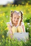 Kleines blondes Mädchen mit digitaler Tablette auf dem gelben Gebiet Lizenzfreie Stockfotos